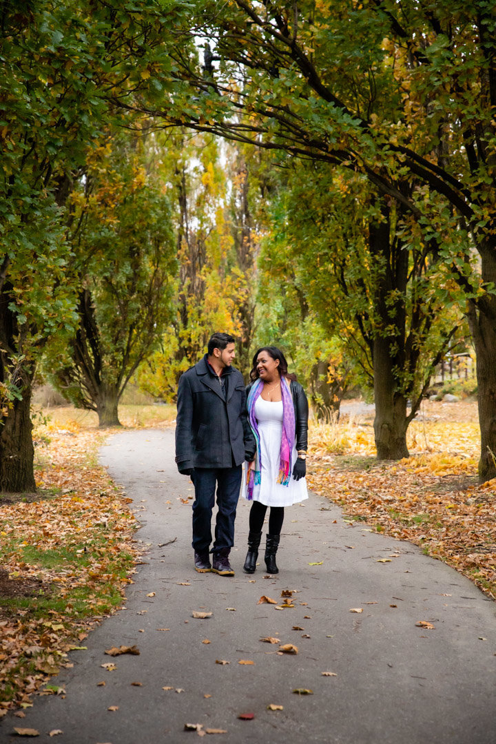 Couple holding hands and walking together in Chinguacousy Park  for Couples Portraits in Brampton