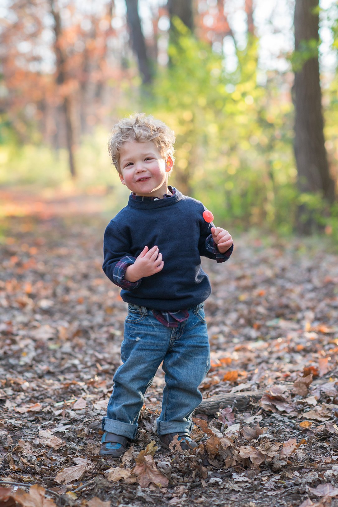 a toddler boy poses with a lollipop in linne woods