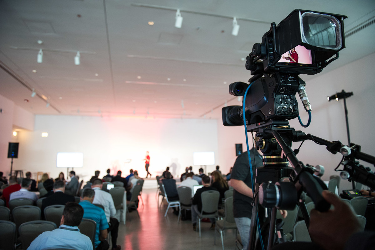 Camera records presenter at Chicago tech summit event.