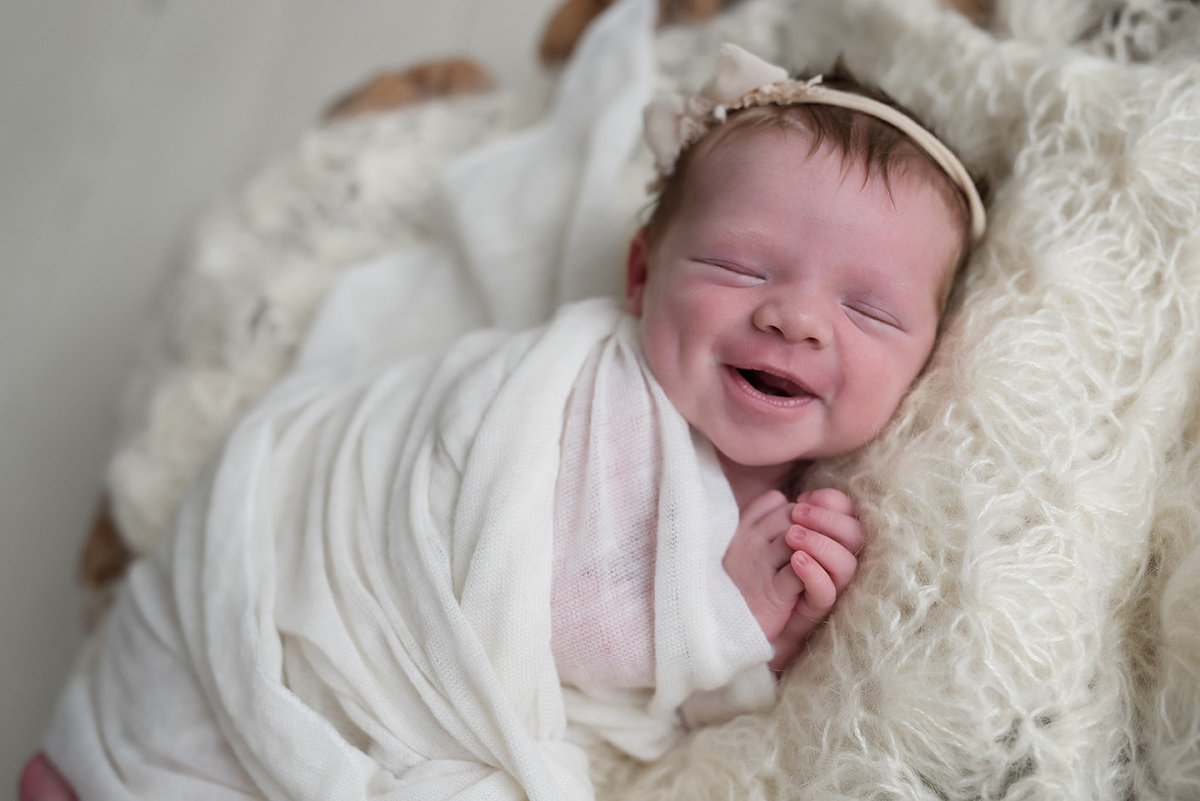 a smiling newborn baby girl in a basket