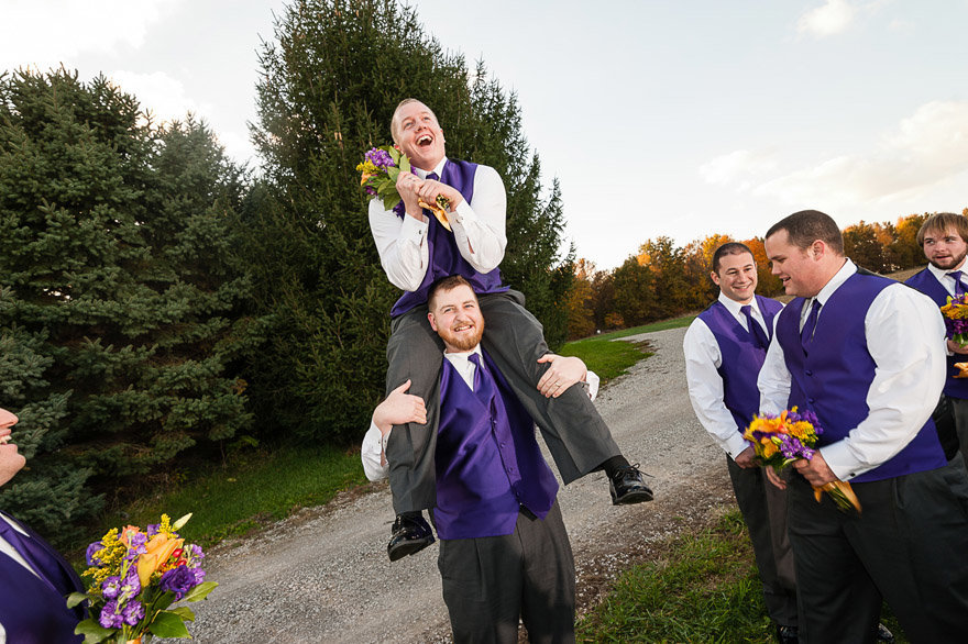 The groom is not exactly sure what to do with the crazy groomsman on his shoulders.