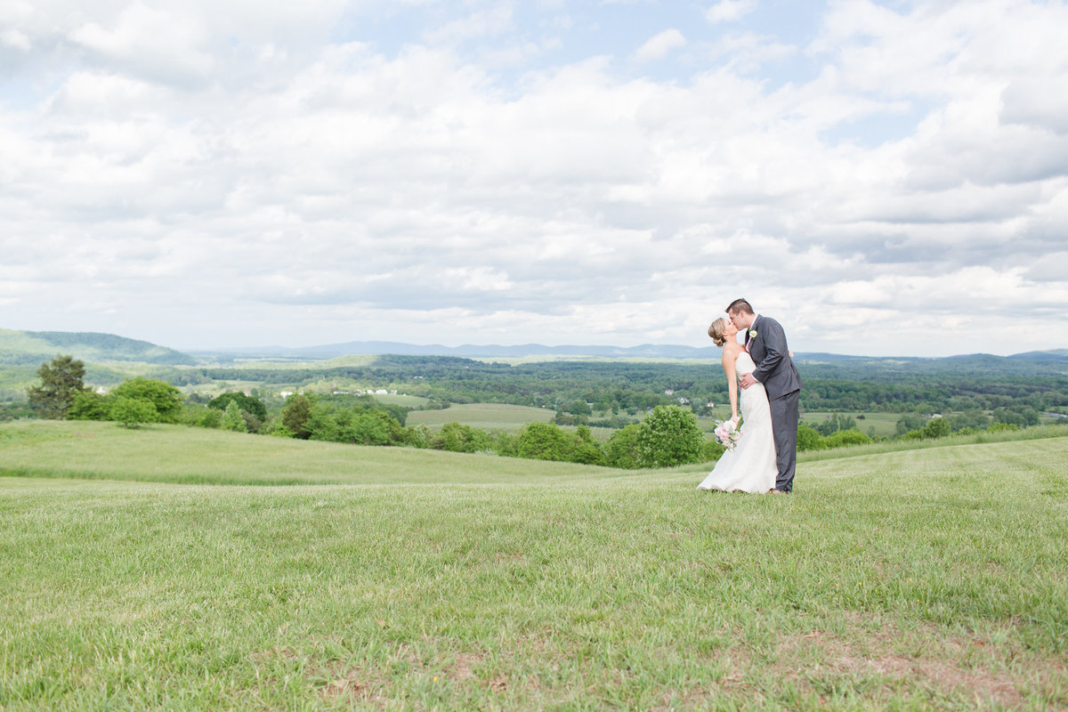 Beautiful newlyweds kissing on a hill overlooking the Shenandoah Mountains.