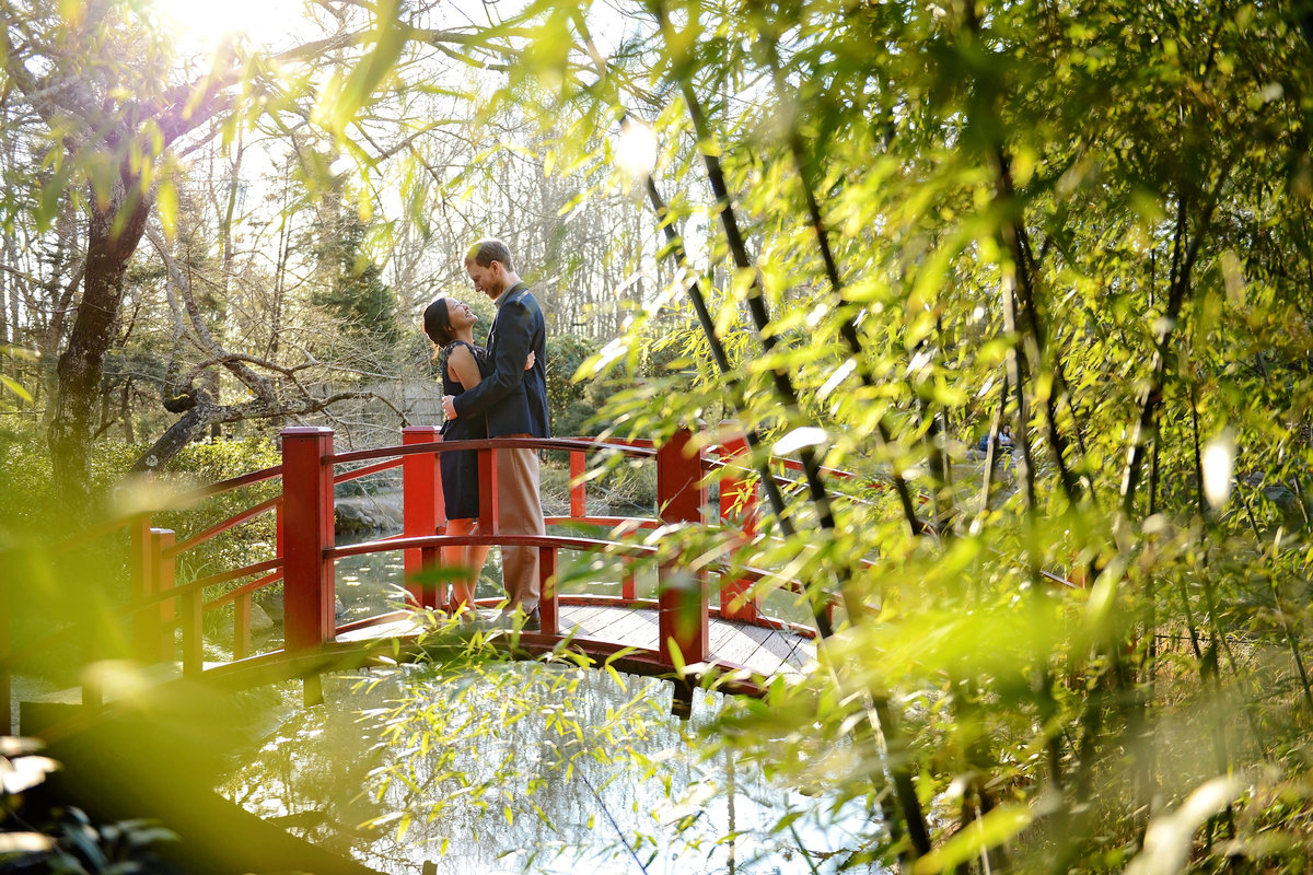 couple cuddling in Birmingham Botanical Gardens engagement session on red bridge