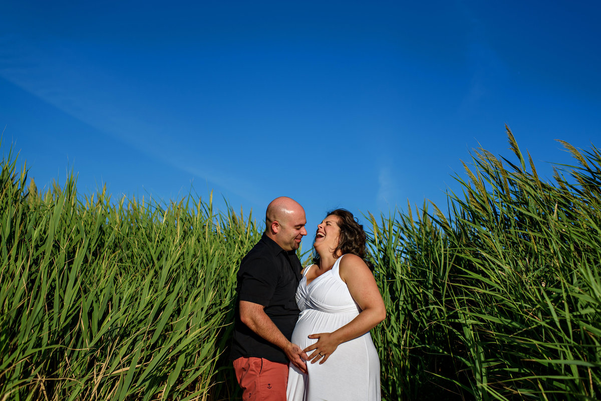 New parents laugh in the tall grass at the beach.
