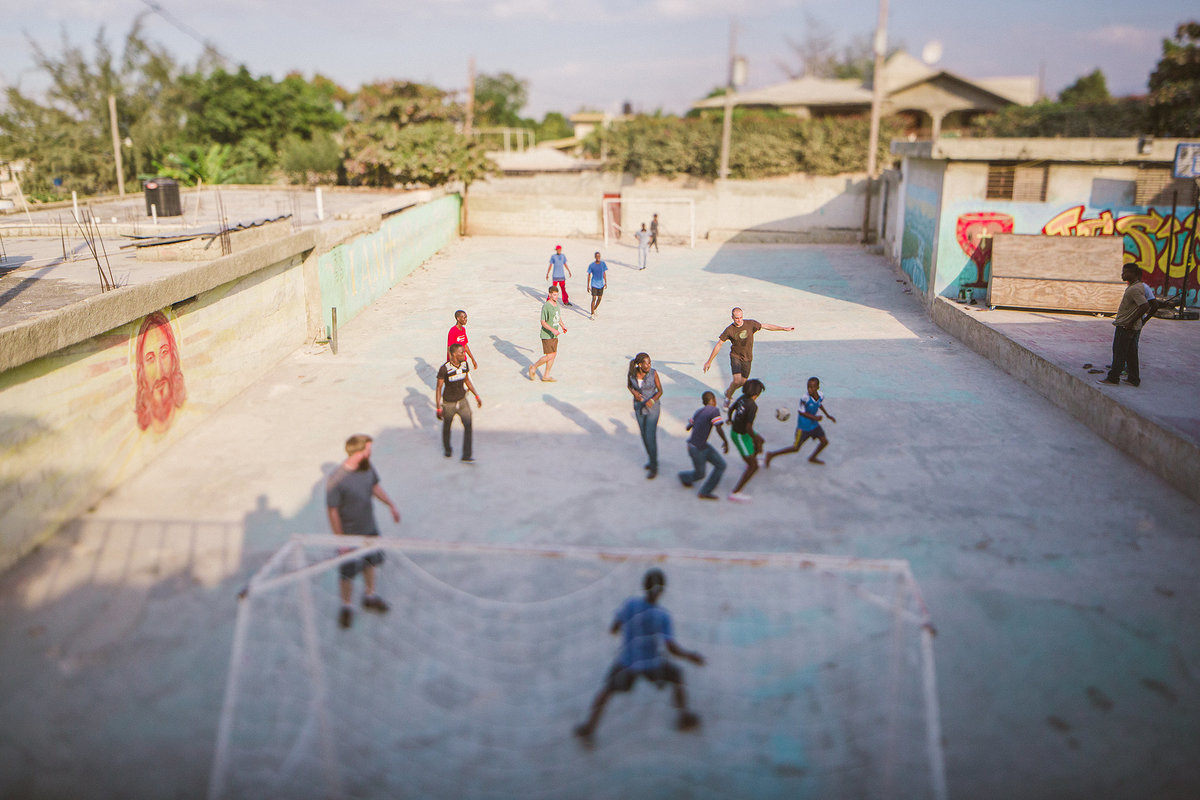 haitian children playing soccer on concrete in haiti