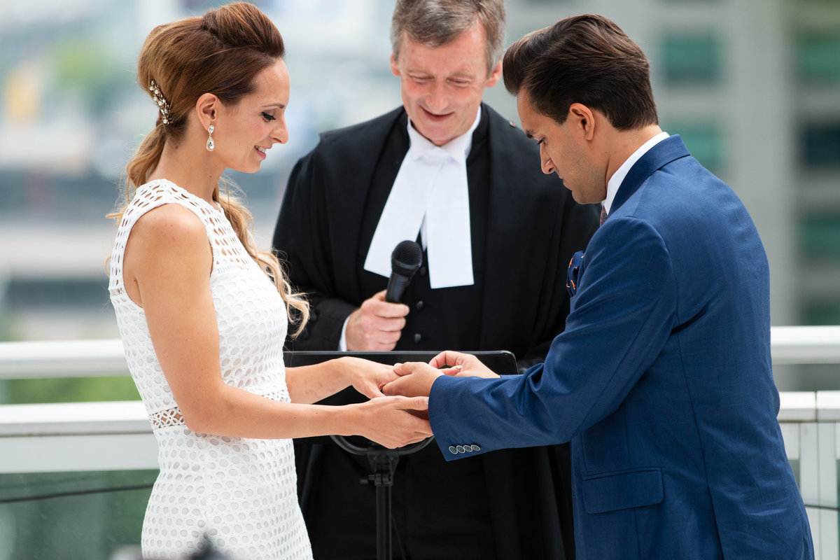 Groom puts the ring on brides finger while she smiles on Toronto Rooftop Wedding Ceremony