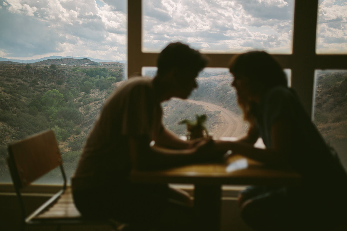 Engaged couple sits at table at Arcosanti with view of the mountains