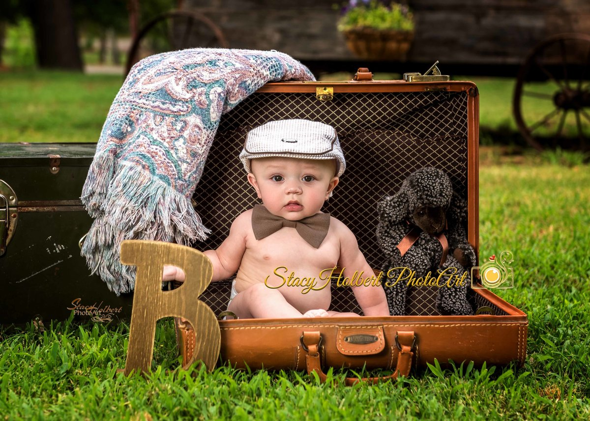 baby in suitcase with hat and bowtie