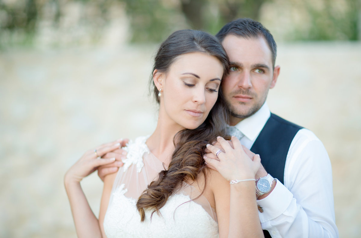 Bride and groom in a romantic soft natural light portrait in Milagros, Spain for this destination wedding where the bride looks down intimately in love and the groom looks in the distance.
