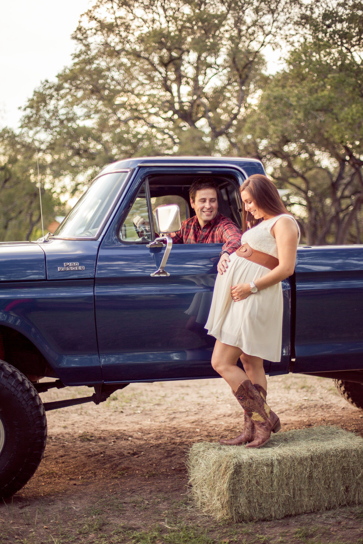 pregnant mother standing on a hay bail and father in s lifted vintage Ford truck for maternity session at park in San Antonio
