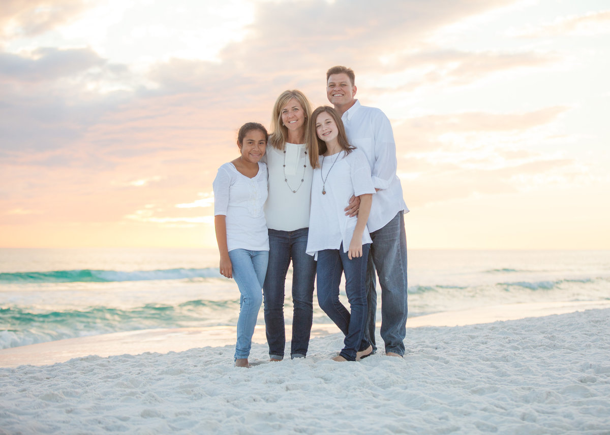 family standing in front of the water on pensacola beach