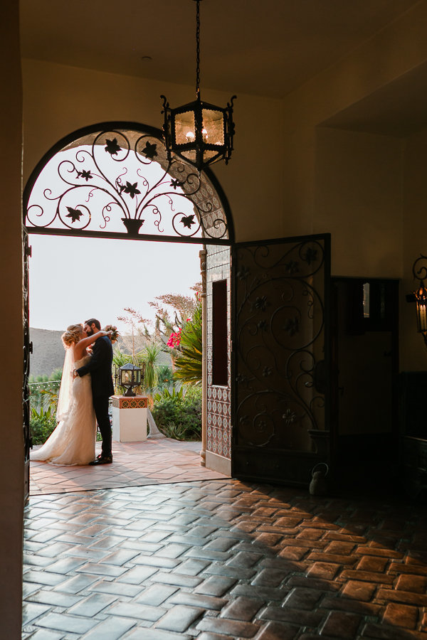 Bride and groom kiss under doorway as sunset sets