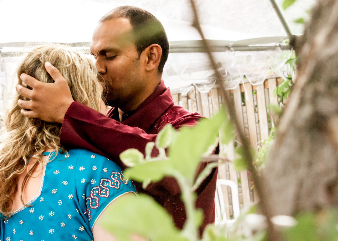 groom sweetly kissing his soon to be wife on the forehead in a private moment in the backyard
