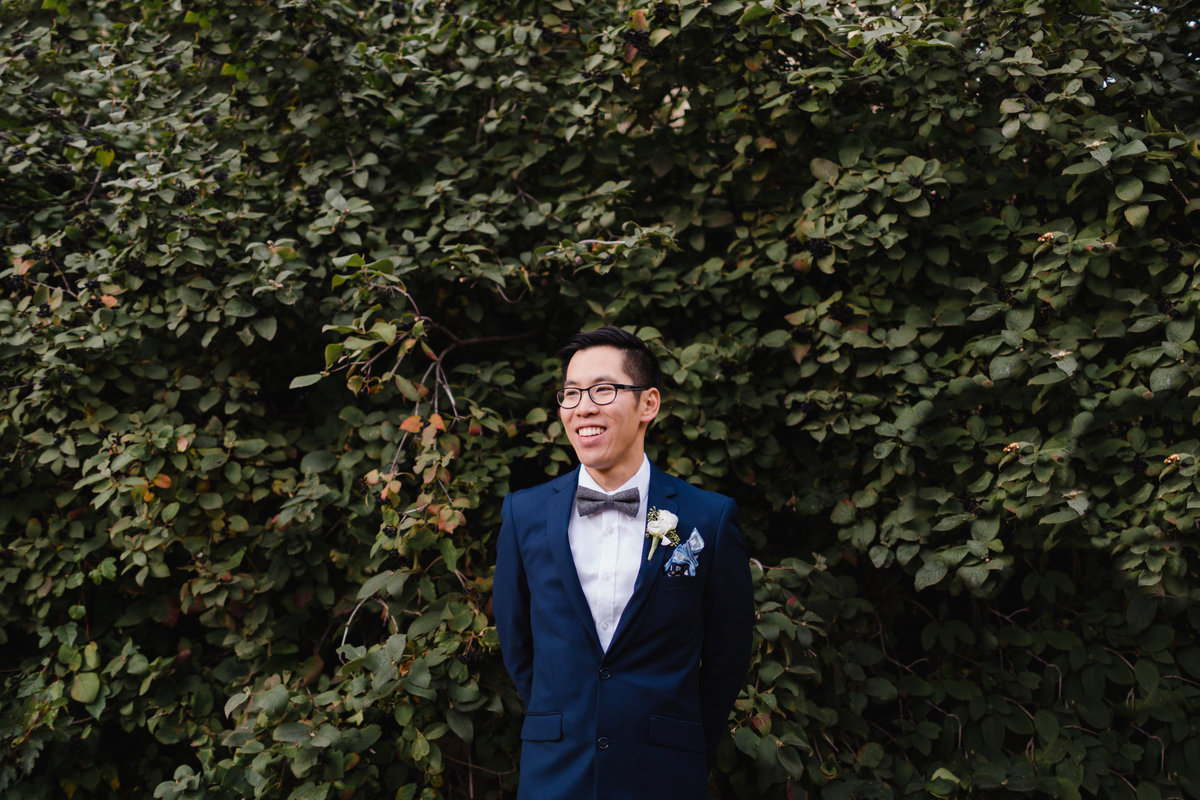 Groom in front of greenery at the University of Saskatchewan