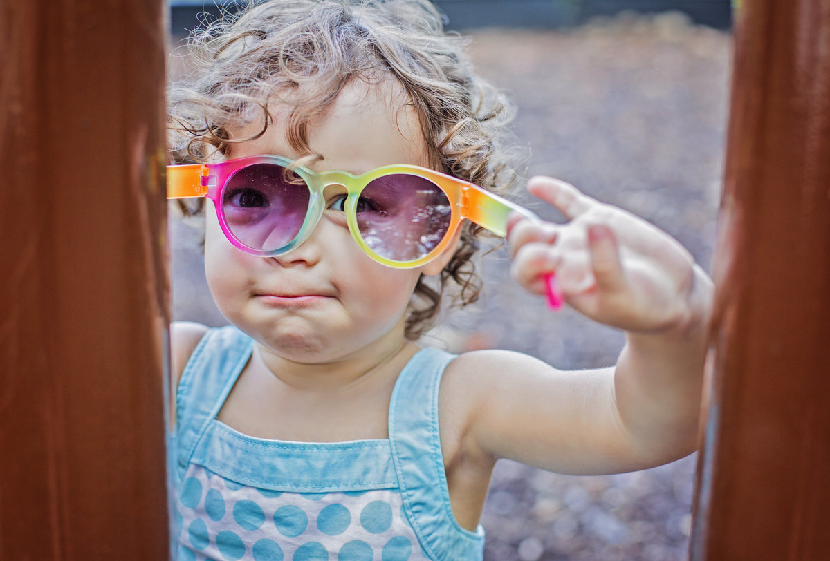 charlotte documentary photographer jamie lucido captures a candid image of a toddler at play with sunglasses