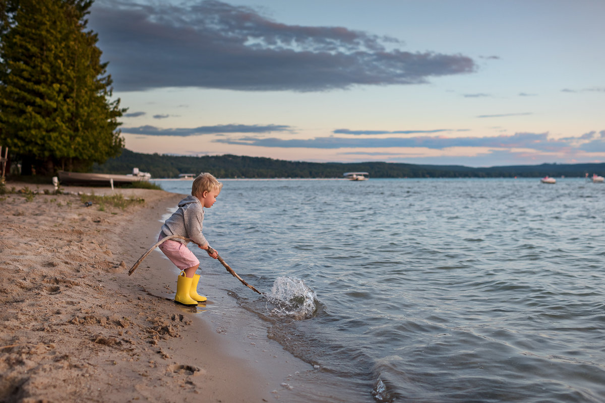 a boy playing in lake michigan with a stick