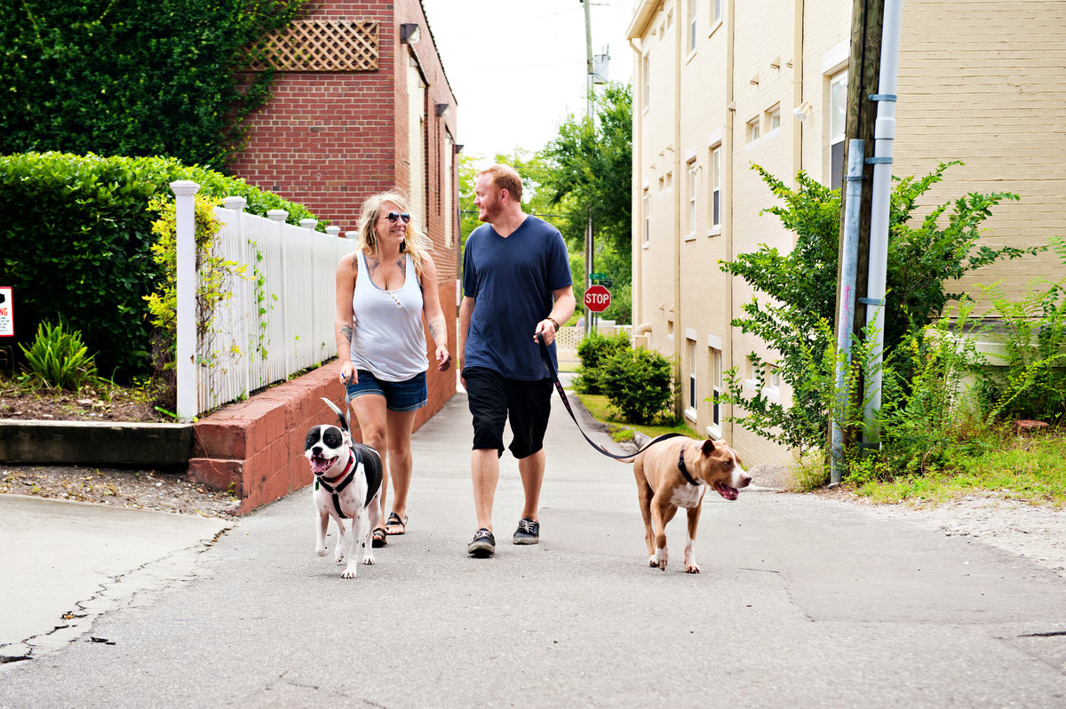 A newly engaged couple walking their dogs in downtown wilmington.