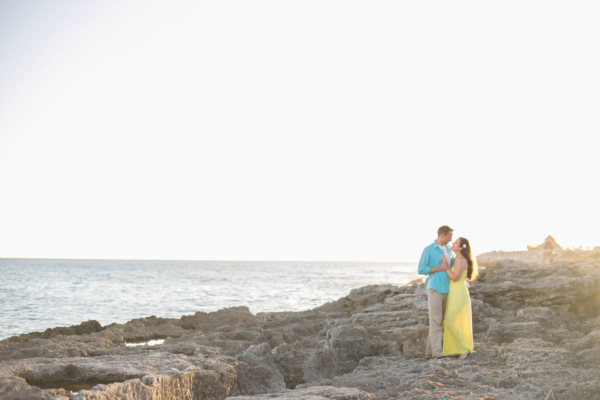 Couple standing on a rocky beach in Mexico for their engagement photos