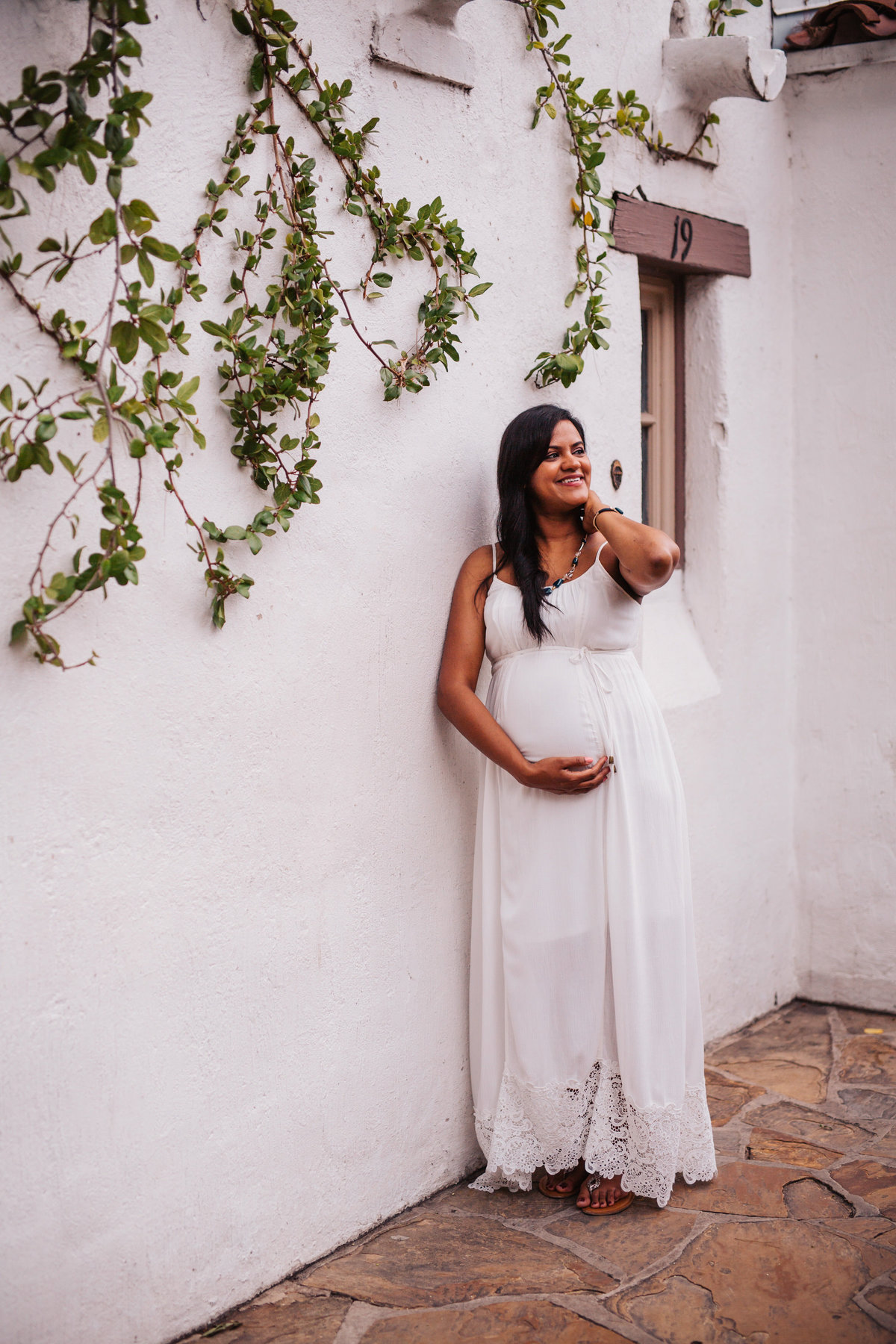 Pregnant woman wearing maternity dress and leaning on wall for her photography shoot.