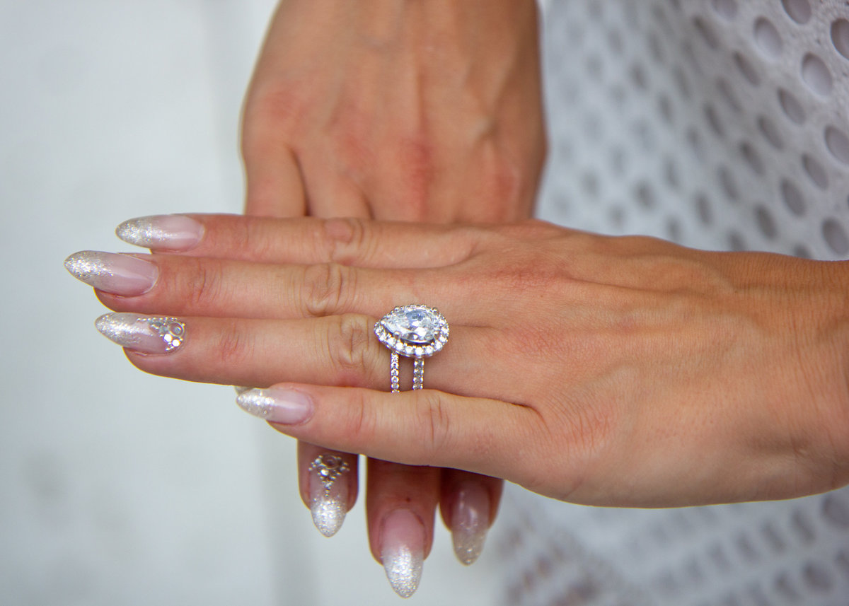 Bride showing off her beautiful teardrop diamond wedding ring at Toronto Rooftop wedding ceremony
