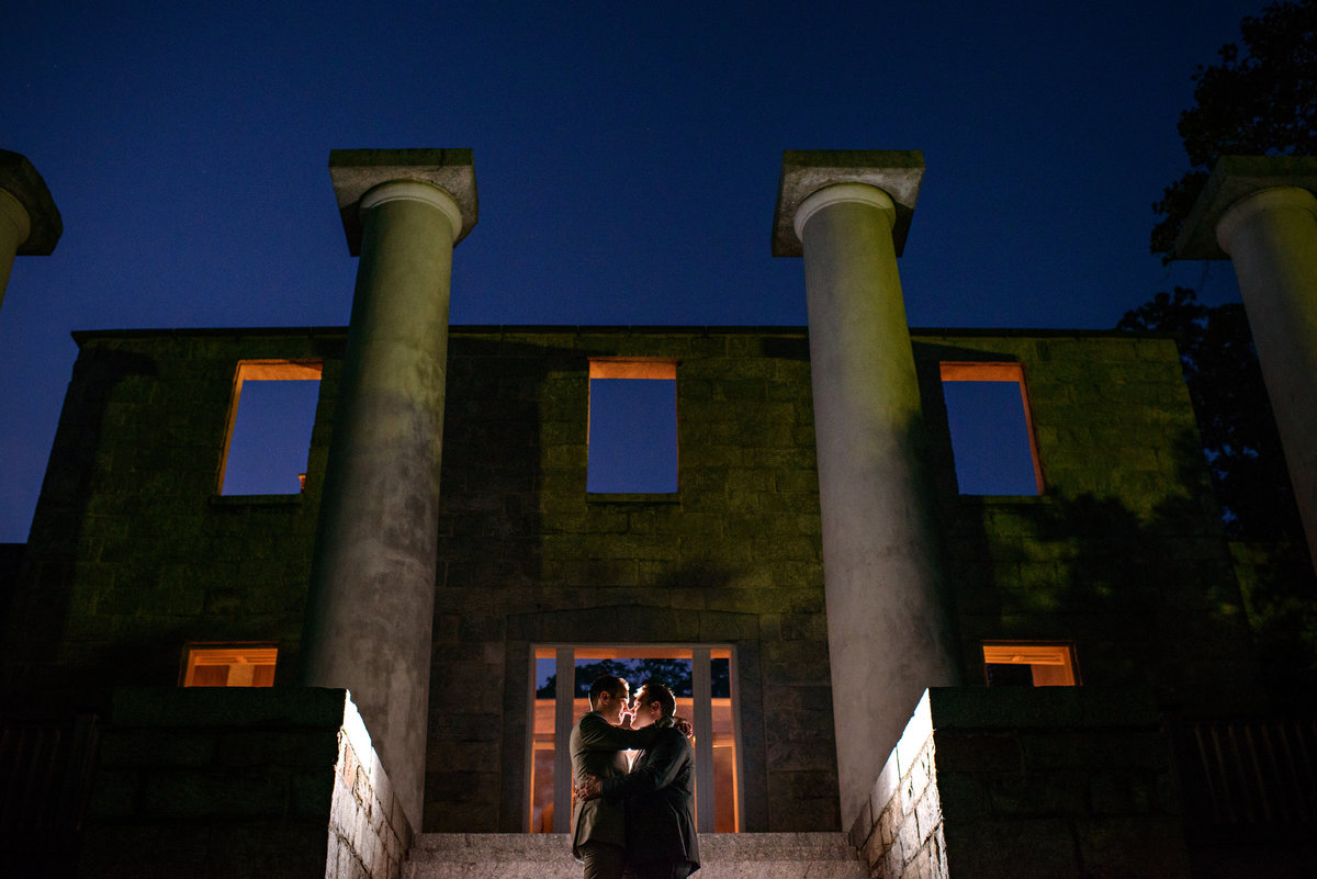A same sex wedding couple hug in front of the ruins of the Patapsco Female Institute.