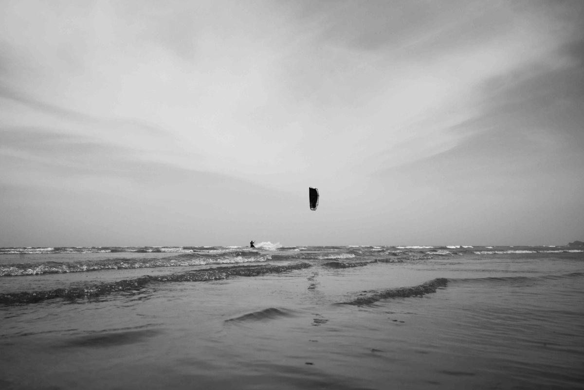 B+W artistic capture of kite surfing kite on the beach nd in the distance. Photo by Ross Photography, Trinidad, W.I..