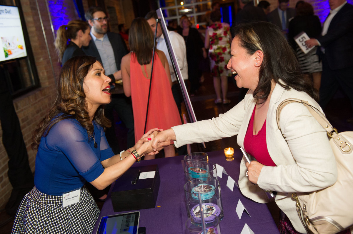 Chicago IL, volunteer at fundraising event greets guest at donation table.