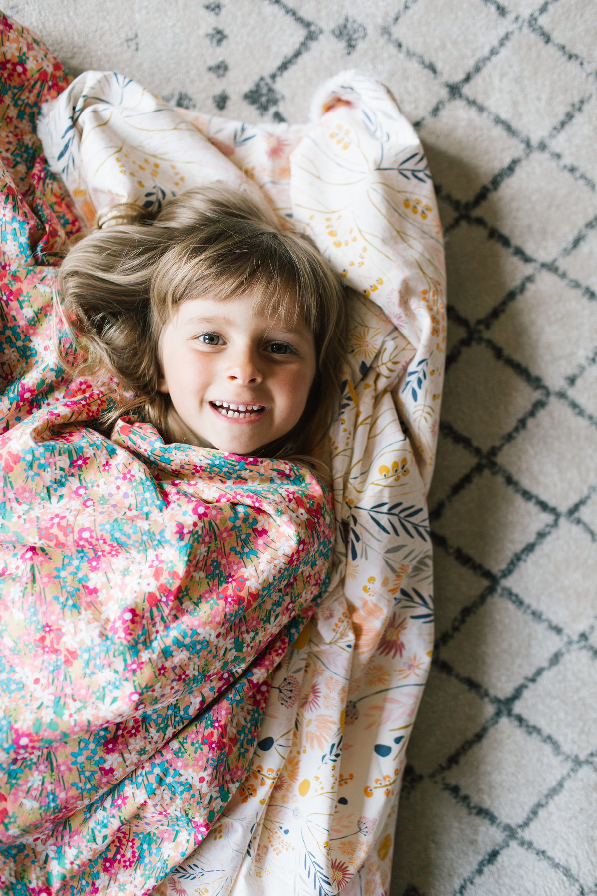 girl wrapped in blanket laying down smiling