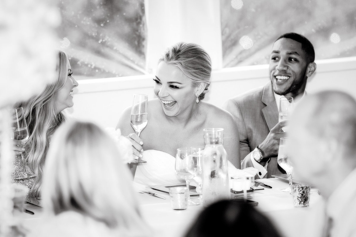 Black and white images of Bride and groom laughing during wedding toasts