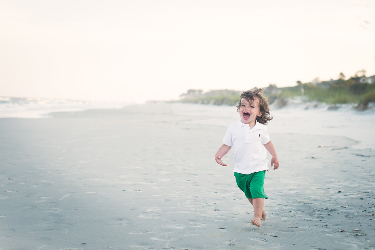 a toddler boy runs into the ocean