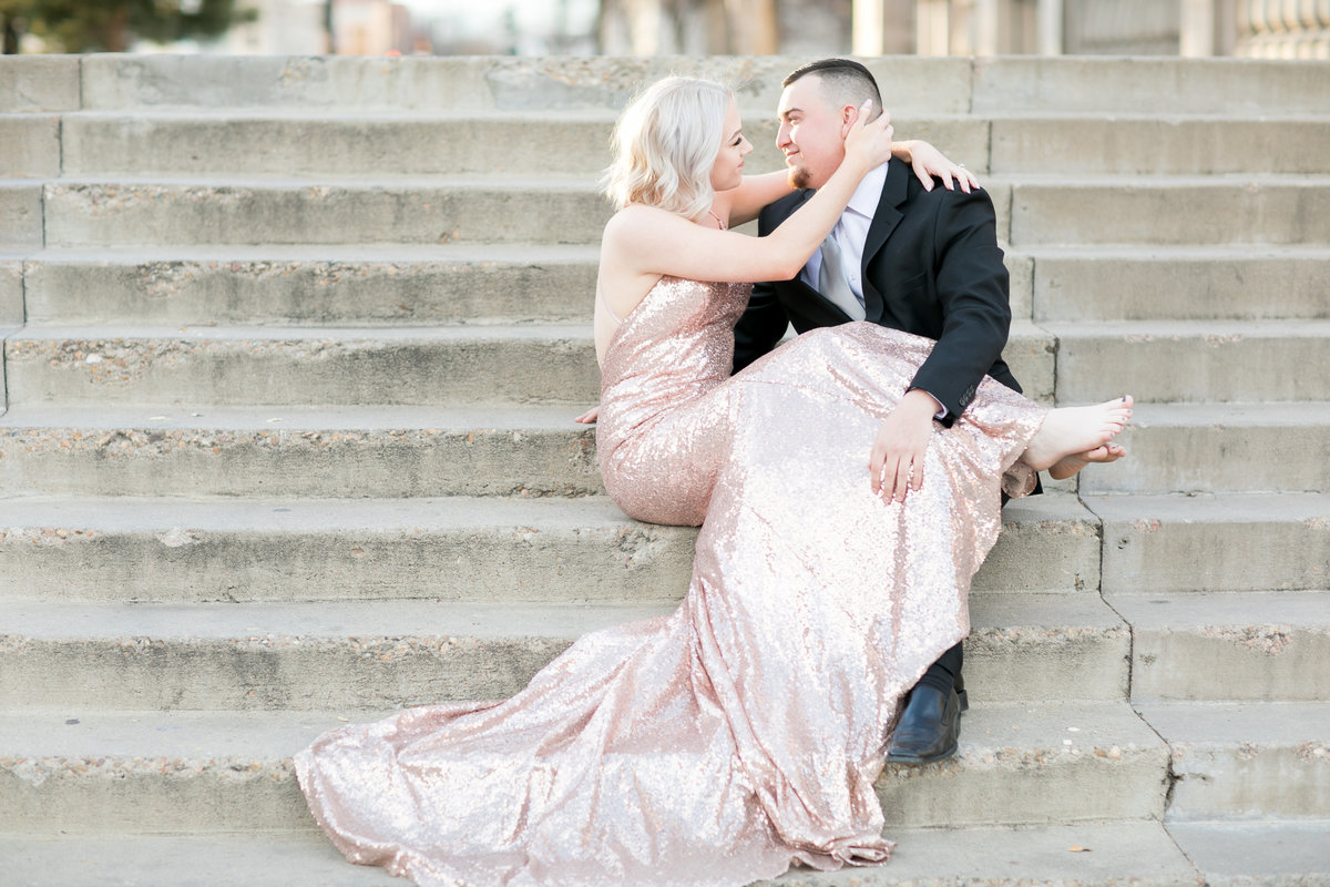 A couple sitting on stairs in a suit and rose gold sequin dress kissing after getting engaged in Colrado