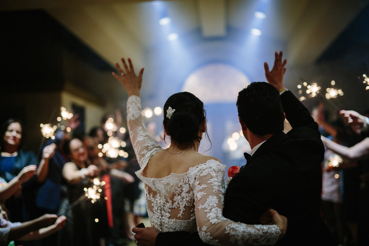 bride and groom wave to guests as they exit wedding reception at Club at Sonterra venue in San Antonio