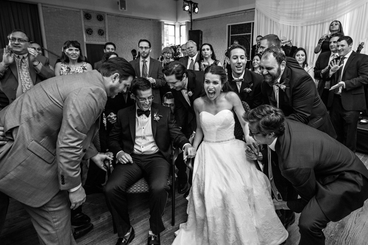 A jewish wedding couple are lifted by wedding guests for The Hora.