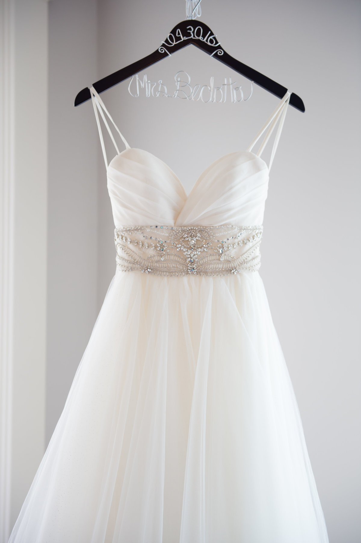 Bride's dress on hanger by Brittany Barclay Photography