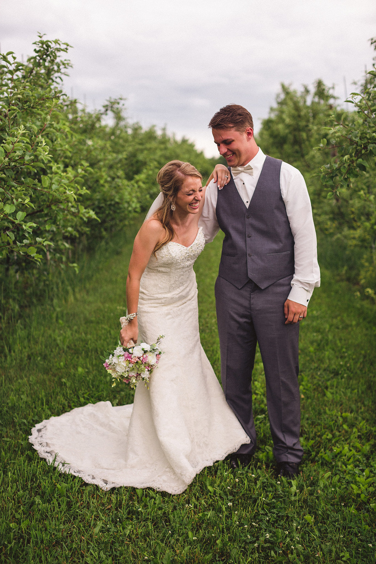 bride and groom laughing together at orchard ridge farms, the pavilion