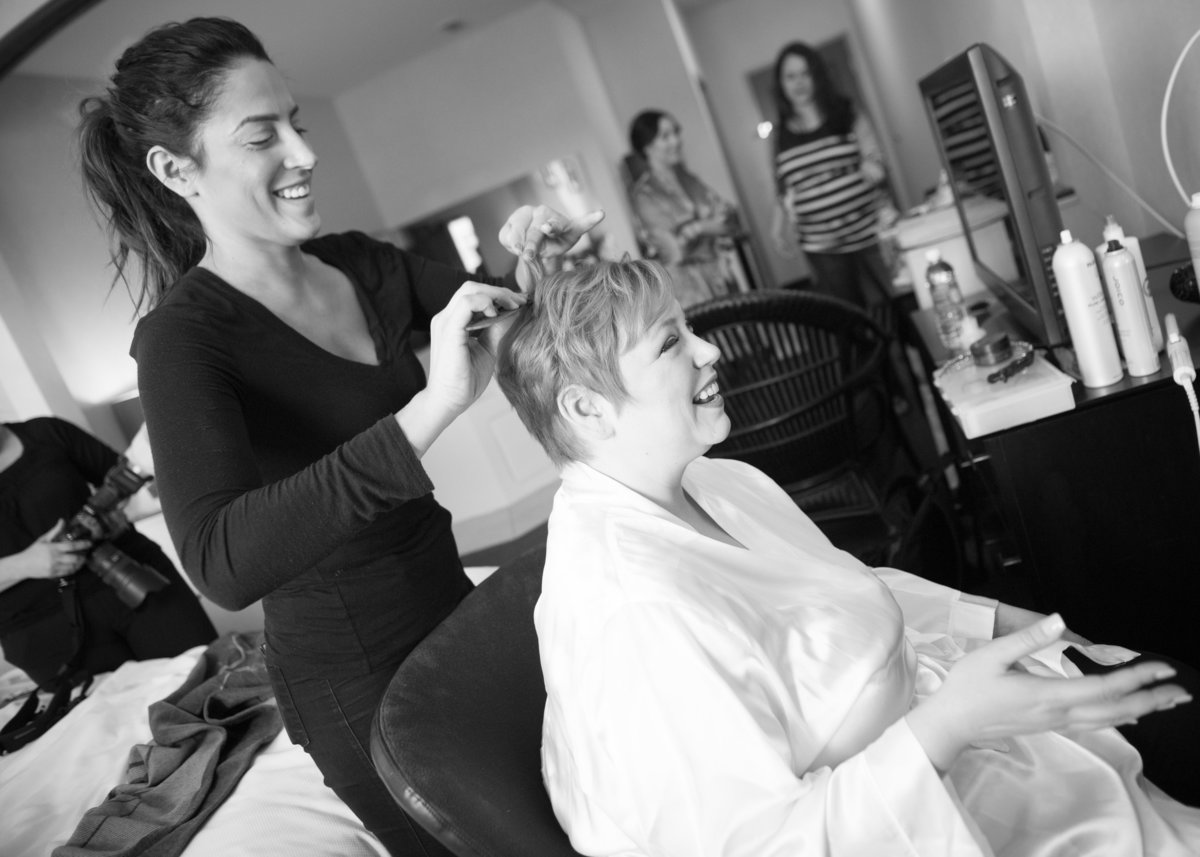 Bride laughs with stylist on wedding morning, Chicago IL.