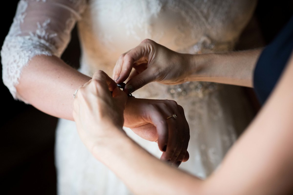 Bridesmaid helps bride put on bracelet, Hocking Hills wedding, Ohio.