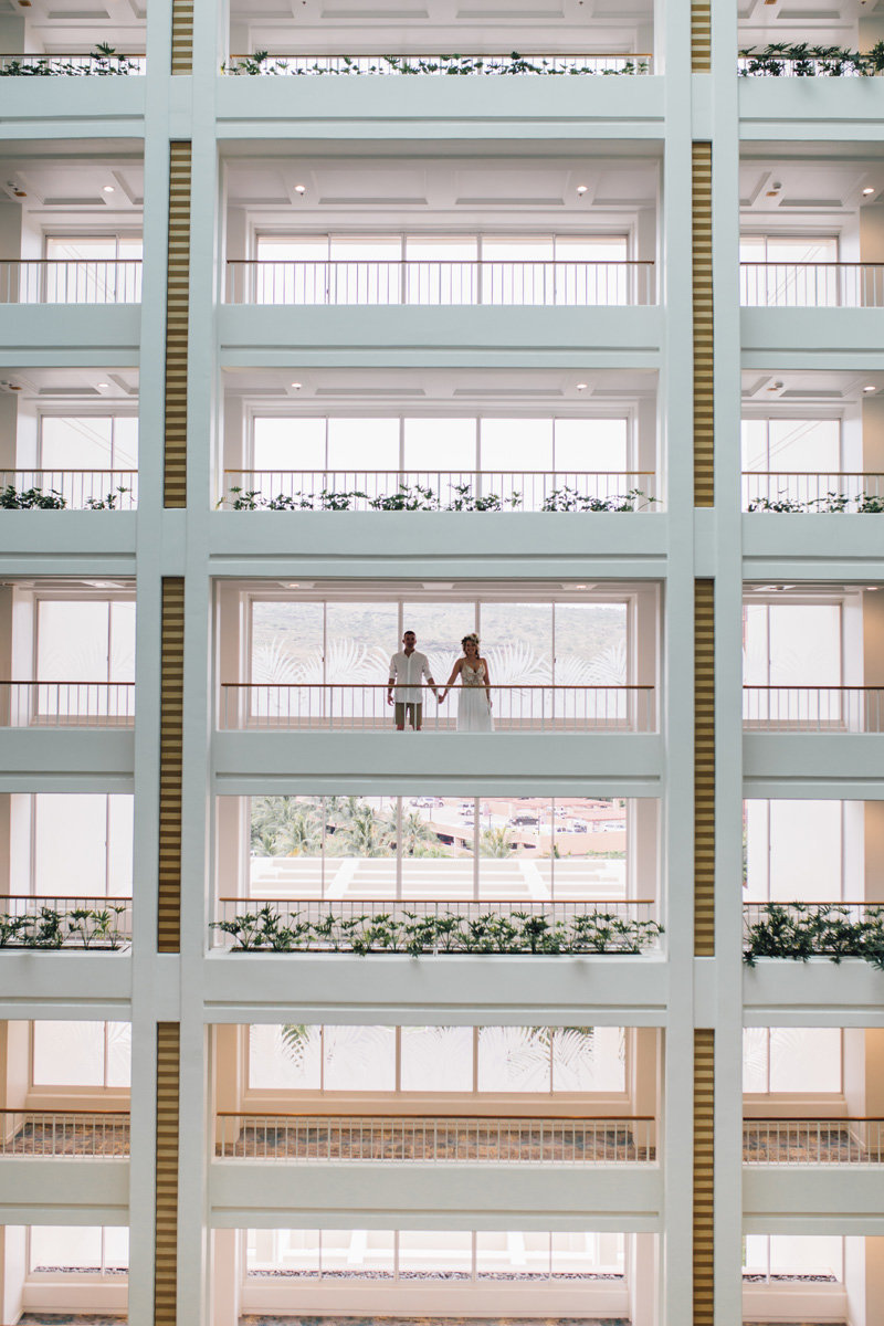 Bride and Groom holding hands in the atrium of Four Season Oahu