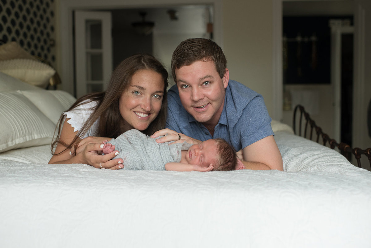 new parents smile with their newborn