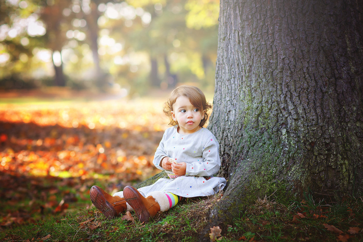 little girl sitting under tree