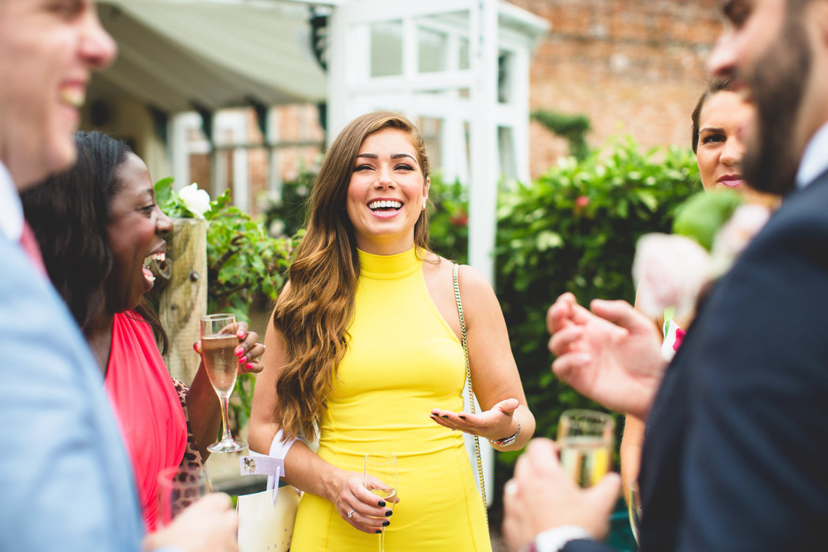 nikki sanderson at a combermere abbey wedding as guest laughing with friends