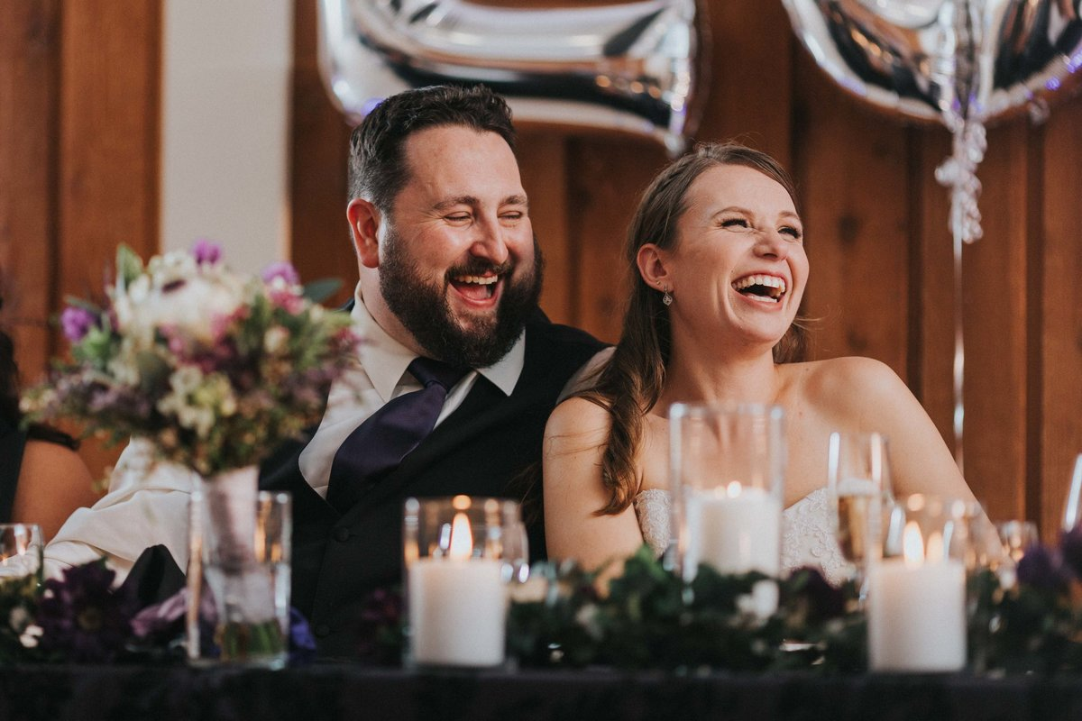 Happy couple sharing a laugh during wedding speech