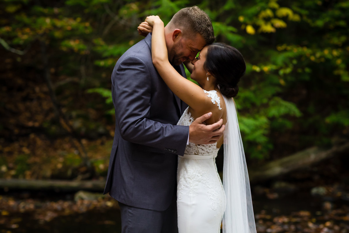Waterville Valley New Hampshire Wedding Photographer Mountains the couple get close in the woods after their ceremony - the bride wears a lace back dress as he holds her tight