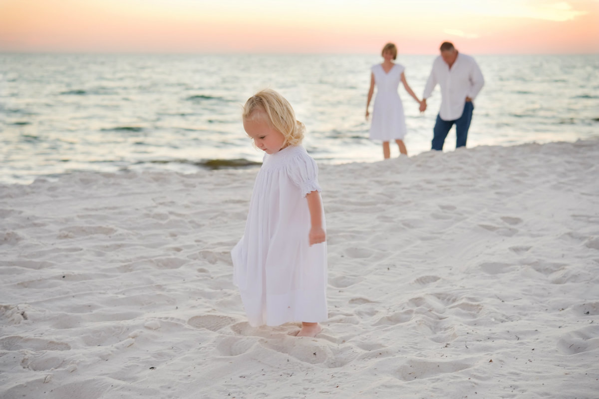 Small child with parents walking on Orange Beach Alabama