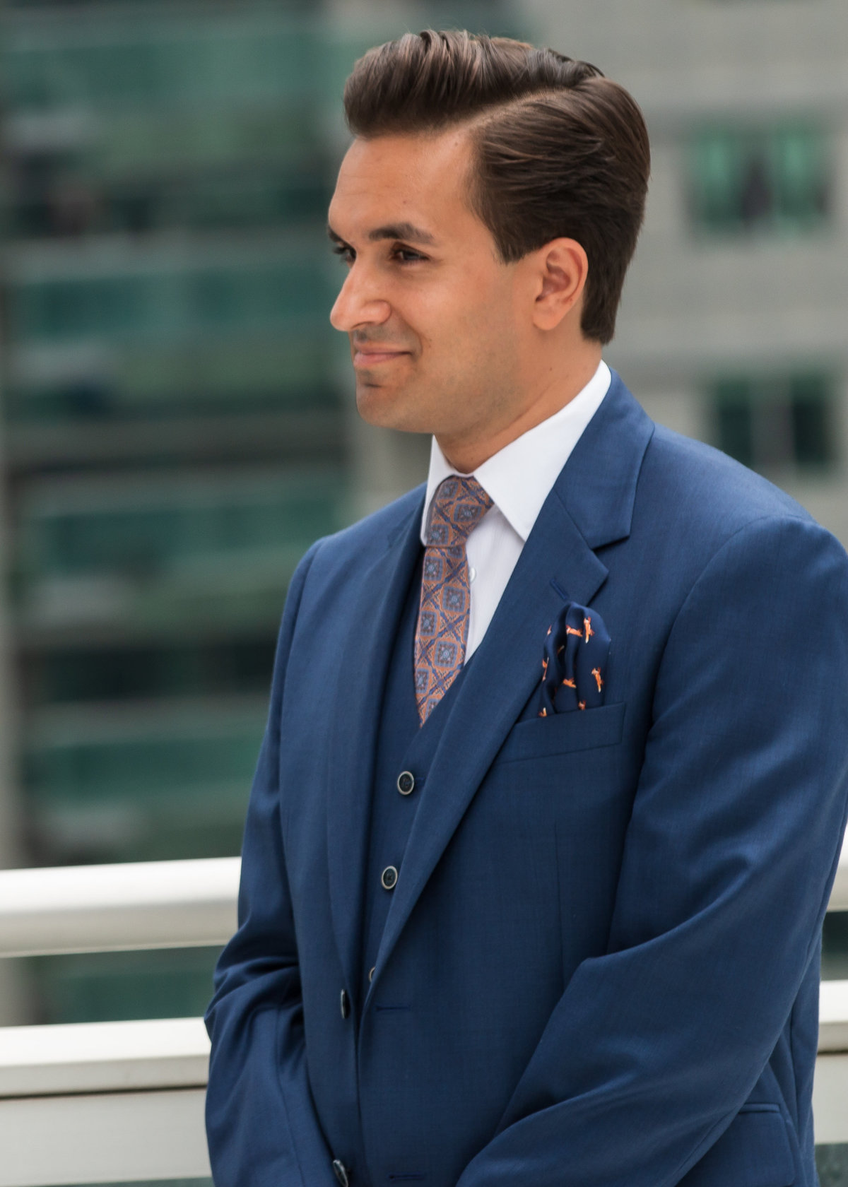 Groom wearing a blue suit smiling at the bride at his Toronto Rooftop Wedding Ceremony