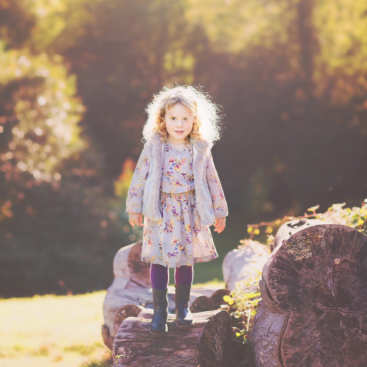 little girl standing on log autumn colours