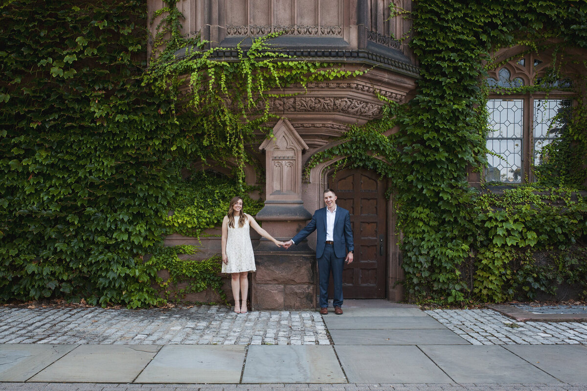 A bride and groom stand in front of a wall of ivy in Princeton, New Jersey