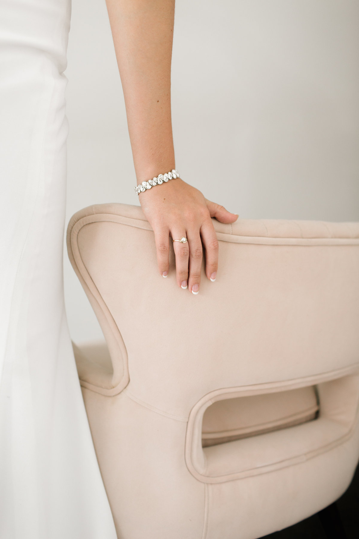 bride hand on pink velvet chair with bracelet