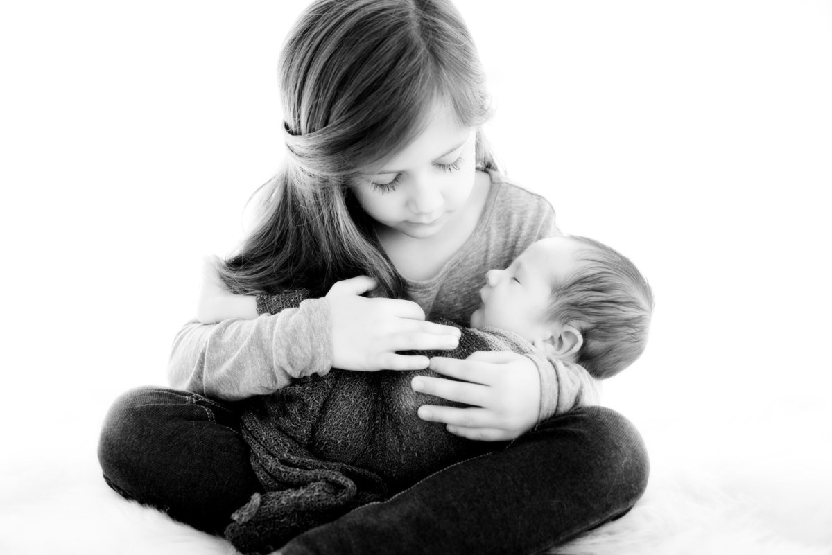 Black and white photo of big sister holding baby brother in her lap embracing him with her arms wrapped around him.