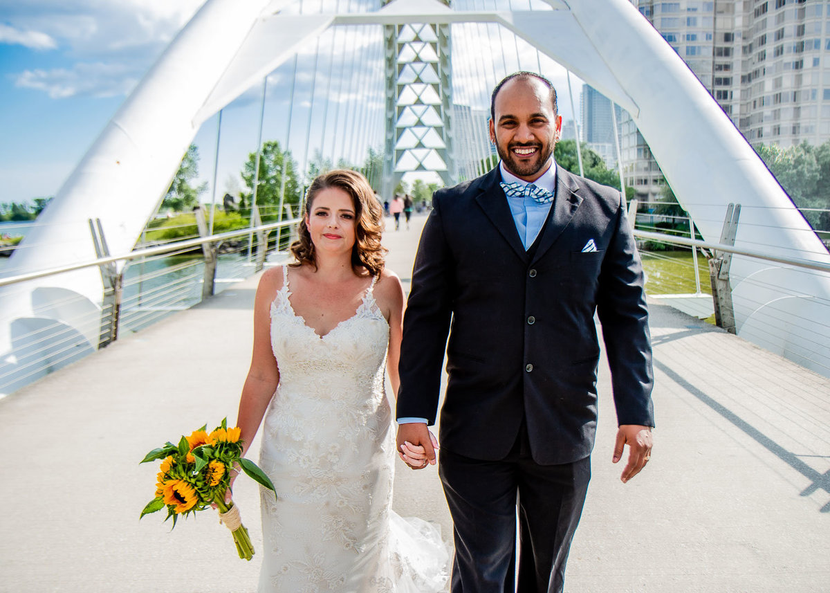 Bride and groom holding hands on the bridge for Toronto Lakeshore Wedding Portraits on the bridge